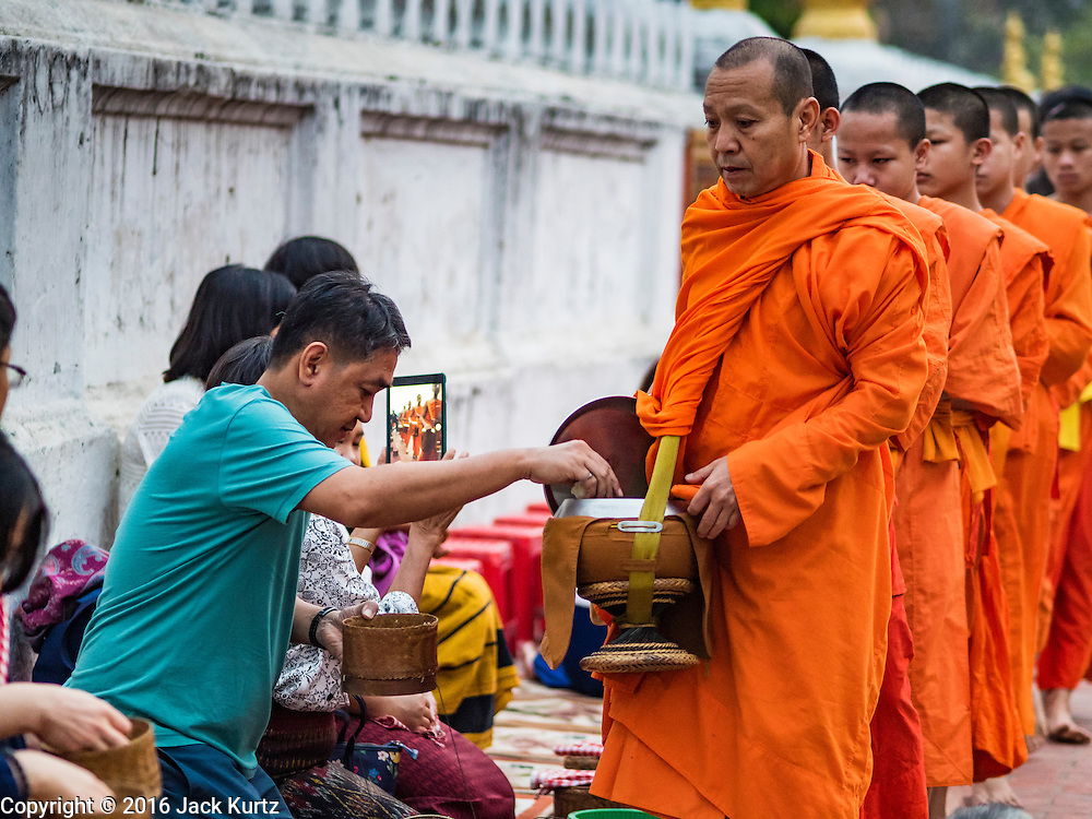 "11 MARCH 2016 - LUANG PRABANG, LAOS:  Tourists give alms to Buddhist monks during the morning tak bat in Luang Prabang. Luang Prabang was named a UNESCO World Heritage Site in 1995. The move saved the city's colonial architecture but the explosion of mass tourism has taken a toll on the city's soul. According to one recent study, a small plot of land that sold for $8,000 three years ago now goes for $120,000. Many longtime residents are selling their homes and moving to small developments around the city. The old homes are then converted to guesthouses, restaurants and spas. The city is famous for the morning ""tak bat,"" or monks' morning alms rounds. Every morning hundreds of Buddhist monks come out before dawn and walk in a silent procession through the city accepting alms from residents. Now, most of the people presenting alms to the monks are tourists, since so many Lao people have moved outside of the city center. About 50,000 people are thought to live in the Luang Prabang area, the city received more than 530,000 tourists in 2014.      PHOTO BY JACK KURTZ"