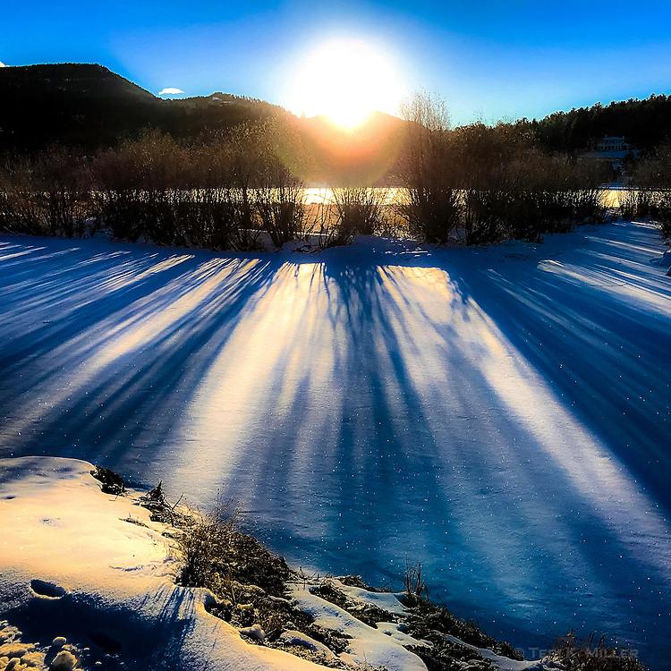 Icy December Dreamscape. Sunrise shadows on the ice at Evergreen Lake, Evergreen, CO.