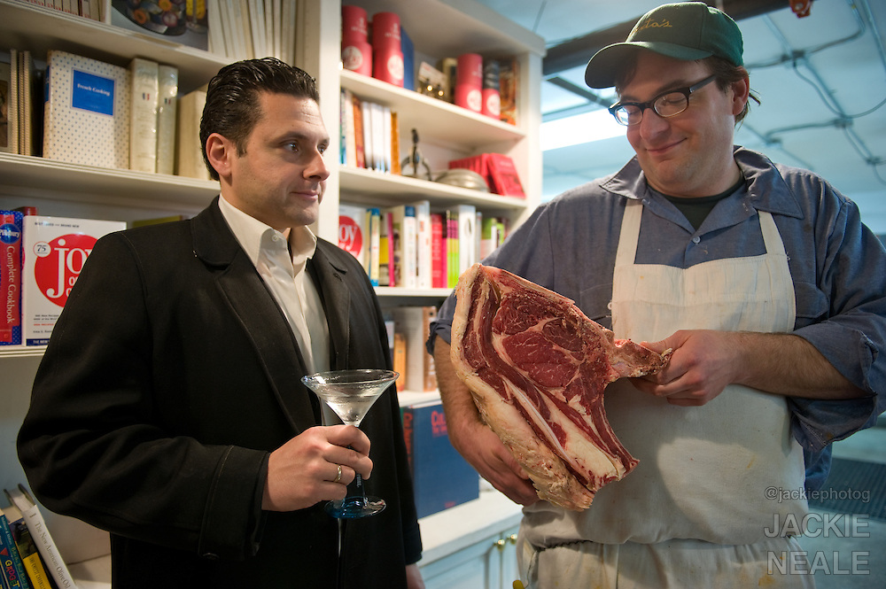 """Tom Mylan holds a highly coveted slab of meat as James Moreland saultes with a Bombay Sapphire Martini.  Tom Mylan and James Moreland collaberate on a dinner party entitled """"Gin and Meat"""" at The Brooklyn Labs, in Williamsburg, Brooklyn, NY.  All drinks made with Bombay Sapphire Gin by James Moreland, and all meat butchered and prepares by Tom Mylan.  Photograph by © Jackie Neale Chadwick"""