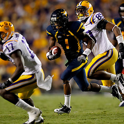Sep 25, 2010; Baton Rouge, LA, USA; West Virginia Mountaineers wide receiver Tavon Austin (1) runs away from LSU Tigers defensive end Lavar Edwards (89) and cornerback Morris Claiborne (17) during the second half at Tiger Stadium. LSU defeated West Virginia 20-14.  Mandatory Credit: Derick E. Hingle