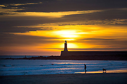 © Licensed to London News Pictures. 25/12/2015. Tynemouth, UK. A dog walker enjoys sunrise on Christmas day on Longhands beach in Tynemouth, north east England. Photo credit: Ben Cawthra/LNP