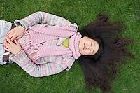 Top view of young Asian woman with long black hair lying on lawn