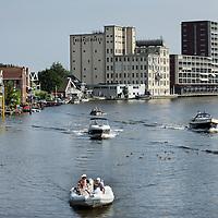 Nederland, Zaandam , 6 juli 2013.<br /> Wandeling door de binnenstad van Zaandam.<br /> Starten bij De Werf aan de Oostzijde. Daarvandaan kun je lopen op een soort boulevard tussen de flats en het water. De eerste stop is De Fabriek, filmhuis en eetcafé met terras aan de Zaan met uitzicht op de sluis. Daarna de sluis zelf.<br /> Dan langs het winkelgebied richting de Koekfabriek: Het oude Verkade pand dat is verbouwd en waar nu de bieb en sportschool en restaurant etc. in zitten.<br /> (Dat is aan de overkant van het startpunt) en misschien nog de Zwaardemaker meepakken aan de Oostzijde. Dat is een oud pakhuis die Rochdale enige jaren geleden heeft verbouwt tot appartementen met een stukje Nieuwbouw.<br /> Ook doen: het Russische buurtje vlakbij de Zaan. Dit jaar staat Rusland in de schijnwerpers en Zaandam heeft een speciale band met Rusland, vanwege het Czaar Peterhuisje en de Russische buurt. <br /> Op de foto: bootje varen over de Zaan met op de achtergrond Monethuis aan de Oostzijde met pand Zwaardemaker erachter.<br /> Foto:Jean-Pierre Jans