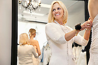 Happy senior owner with pincushion in wrist helping bride getting dressed
