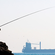 A man fishes on the coast of Taejongdae, a natural park in the port city of Busan, South Korea.