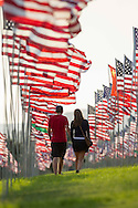 A couple walk through amongst 3,000 US flags are displayed at Pepperdine University to mark the 12th anniversary of the 9/11 terror attack, September 10, 2013 in Malibu, California. Photo by Ringo Chiu/PHOTOFORMULA.com)