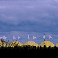 Beach tents stand with flags waving as an autumn storm approaches along the Atlantic Ocean at Cape May, New Jersey.