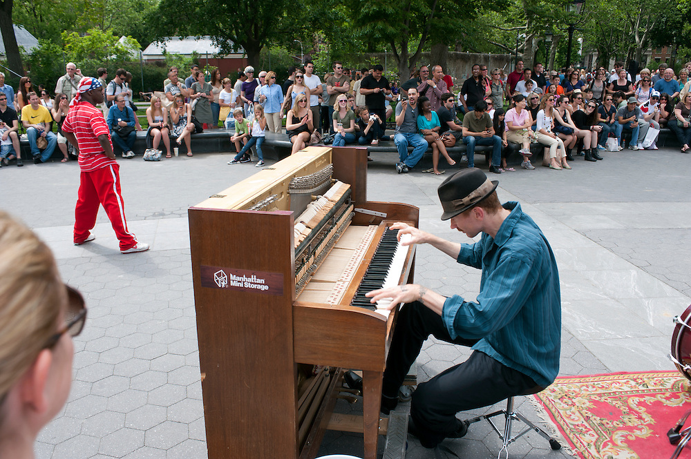 "Colin Huggins wird ""the crazy piano guy"" genannt. Er schleppt sein Klavier durch ganz New York um eine geeignete Stelle zum Spielen zu besetzen. Er ist der einzigste Musiker in der Stadt welcher sein Klavier auch in der Ubahn spielt. Stationen mit Fahrstuehlen ermoeglichen die Schwerstarbeit. Im Sommer zieht es ihn meist in den Washington Square Park, wo er oft mit anderen Schaustellern zusammenarbeitet...Jedes Jahr im Mai laden die Betreiber der New Yorker Subway (MTA) ca 60 Musiker und Gruppen zu einem Wettbewerb im Grand Central Station ein. Die Gewinner duerfen ganz legal an ihnen zugeteilten Orten im Ubahn System auftreten. Viele unangemeldete  und selbst organisierte Musiker jeder nur erdenklichen Musikrichtung spielen zudem in fast jeder wichtigen Ubahnstation. Die Angst vor der Polizei ist dabei gering, selten gibt es eine Verwarnung und noch seltener ein Bussgeld. Meist wird einfach der Ort gewechselt falls es Probleme gibt...Colin Huggins is 'known as 'the crazy piano guy'. He drags his piano all over New York and is the only known musician who plays the piano even on subway platforms. During the summer months he prefers to perform in Washington Square Park where he often joins other artists who happen to show their talent that day...Drummer Mike Alaska on the L train platform at Union Square Station in Manhattan. The L train attracts many musicians...MTA (Metropolitan Transportation Authority) .Music Under New York.Auditions.Every Spring, Music Under New York (MUNY) presents a day of auditions in Grand Central Terminal to review and add new performers to the MUNY roster. This year, MUNY held its annual auditions in May on the Northeast Balcony of the Grand Central Terminal. .In addition legions of non-official musicians play in New Yorks subway stations and on platforms. One can find every thinkable style and instrument underground. ..Foto: Stefan Falke."