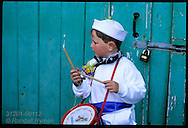 Drummer boy in white wears blue sash, color of the Peace Oss, one of two May Day hobby horses in Padstow, Cornwall, England