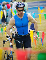 Mid 30's Caucasian man running with his bike in the swim to bike transition area of a triathlon race.<br />