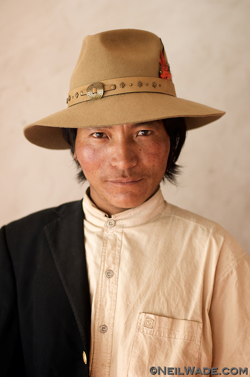 A Tibetan man wearing nice clothes poses for a photograph in Yushu, Tibet.