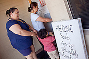 20 JUNE 2009 - PHOENIX, AZ: Mireya Renteria and others walk into the clinic at the Cultural Cup. The walk in clinic at the Cultural Cup Food Bank started two years ago when Cultural Cup founder Zarinah Awad wanted to expand the food bank's outreach and provide basic medical care for the people who use the food bank. The clinic sees, on average, 7 - 11 patients a week. Awad said that as the economy has worsened since the clinic opened and demand has steadily increased. She attributes the growth to people losing their jobs and health insurance. The clinic is staffed by volunteers both in the office and medical staff. Adults are seen every Saturday. Children are seen one Saturday a month, when a pediatrician comes in. Awad, a Moslem, said the food bank and clinic are rooted in the Moslem tradition of Zakat or Alms Giving, the giving of a small percentage of one's income to charity which is one of the Five Pillars of Islam.   PHOTO BY JACK KURTZ