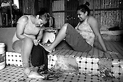 Laura takes time out of cooking and cleaning to spend some much needed girl time with her friend Vanesa. They paint each other nails while their children sit in the background watching television.