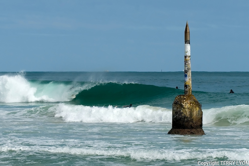 A surfer inside the tube by the cottesloe pylon