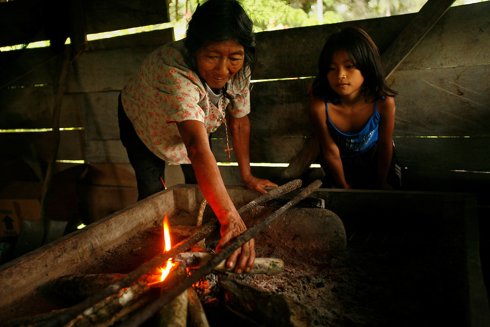 An older woman and a child start a fire near San Pedro Sumino in August of 2009.    Her children have left, she lives with her granddaughter. At night they both go to a neighbors house where they get fed.
