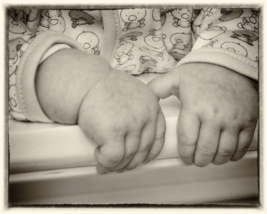 Infant's hands on a crib