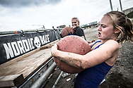 During the Nordic Race event at Refshaleøen in Copenhagen, a female competitor battles to lift a stone sphere up on to a wooden platform as her friend looks on -<br />