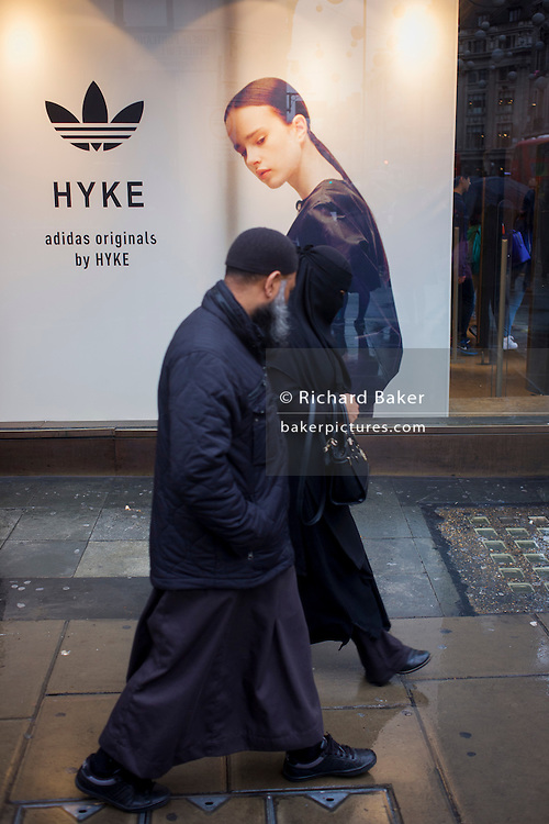 Model on an Adidas seemingly looks over her shoulder to watch muslim passers-by on Oxford Street, London.