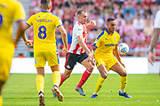 Terell Thomas (#6) of AFC Wimbledon shields the ball from Charlie Wyke (#9) of Sunderland AFC during the EFL Sky Bet League 1 match between Sunderland and AFC Wimbledon at the Stadium Of Light, Sunderland, England on 24 August 2019.
