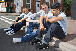 Group of teenaged boys sitting on a street corner chatting,