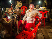"""06 DECEMBER 2015 - BANGKOK, THAILAND: A Chinese opera performer relaxes in her dressing room before going on stage at the Ruby Goddess Shrine in the Dusit district of Bangkok. Chinese opera was once very popular in Thailand, where it is called """"Ngiew."""" It is usually performed in the Teochew language. Millions of Chinese emigrated to Thailand (then Siam) in the 18th and 19th centuries and brought their culture with them. Recently the popularity of ngiew has faded as people turn to performances of opera on DVD or movies. There are about 30 Chinese opera troupes left in Bangkok and its environs. They are especially busy during Chinese New Year and Chinese holidays when they travel from Chinese temple to Chinese temple performing on stages they put up in streets near the temple, sometimes sleeping on hammocks they sling under their stage.     PHOTO BY JACK KURTZ"""