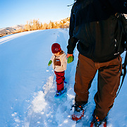 A toddler and her father snow shoe in late afternoon light near Vail, Colorado.