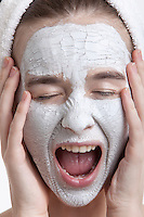 Frustrated young woman with face pack screaming against white background