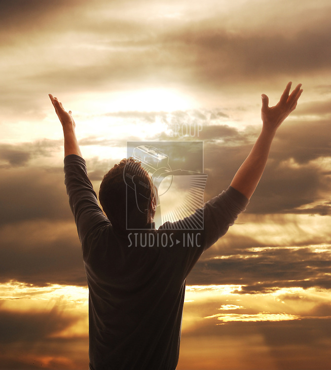 Man holding arms up in praise against golden sunset