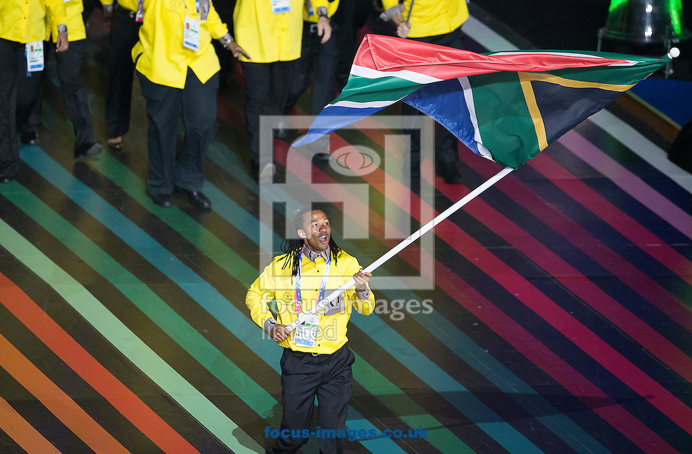 South Africa's flagbearer Cecil Sebastian Afrika ( C ) leads the team during the Glasgow 2014 Commonwealth Games Opening Ceremony at Celtic Park, Glasgow<br /> Picture by Paul Terry/Focus Images Ltd +44 7545 642257<br /> 23/07/2014