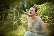 Woman in a summer dress, sitting in front of ferns in Cheddar Gorge.