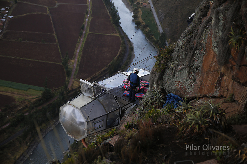 Tourists enjoy food inside a transparent cabine at the Skylodge Adventure Suites in the Sacred Valley in Cusco, Peru, August 14, 2015. The Skylodge is composed by three capsule suites hanging at the top of the 1200 ft mountain with a 300 degree view of the Valley. To sleep at Skylodge, people must climb 400 mt. of Via Ferrata path or hike a trail through ziplines. REUTERS/Pilar Olivares