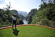 """ZHANGJIAJIE, CHINA - SEPTEMBER 23: (CHINA OUT) <br /> <br /> <br /> """"Extreme 19th-Golf Hole""""<br /> <br /> A worker of Korea experiences golf on the tee of """"Extreme 19th-Golf Hole"""" on September 23, 2014 in Zhangjiajie, Hunan province of China. A 200-meter long """"Extreme 19th-Golf Hole"""" was established at Baofeng Lake Scenic Area of Zhangjiajie whose 248-square-mters tee is atop a 80-meter cliff with its putting green floating on Baofeng lake. The first """"Extreme 19th-Golf Hole"""" challenge race.<br /> ©Exclusivepix"""