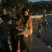 """A young man towels off after swimming at the beach in Vung Tau, Vietnam, a popular beach resort a few hours' drive from Ho Chi Minh City. Former glam rock star Gary Glitter is currently behind bars in the resort town, facing charges of child molestation. Glitter, whose real name is Paul Gadd, was convicted in Britain in 1999 of possessing child pornography and served two months in jail. In 2002 he was kicked out of Cambodia, a country with lax regulation of prostitution. Glitter's 1970's hit """"Rock and Roll (Part 2)""""  is played regularly at sporting events throughout North America and Europe."""