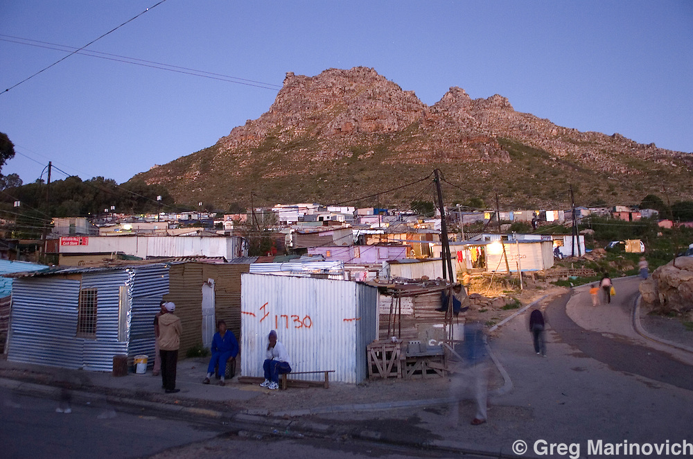 Night falls on Imizamo Yethu shanty town, Hout Bay, Cape Town, South Africa. The work of the CPF and neighbourhood watch have seen the crime rate in Hout Bay drop 63%, but relations between the shanty town of Imizamo Yethu and Hout Bay are tense.  photo  Leonie Marinovich