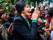 05 AUGUST 2016 - BANGKOK, THAILAND:  YINGLUCK SHINAWATRA greets people while she walks through a mob of supporters at the Supreme Court of Thailand Friday. She appeared in court to start her legal defense. She was deposed by a military coup in 2014 and is being tried on corruption and mismanagement charges related to a price support plan for Thai rice farmers that was instituted while she was Prime Minister. More than two years after her government was deposed by a military coup, she is still a popular figure and hundreds of her supporters packed the area around the courthouse to greet her when she arrived at the Court.      PHOTO BY JACK KURTZ