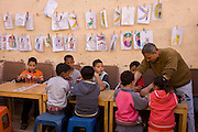 Local schoolchildren learn to play memory card games at the American-sponsored Theban Mapping Project Library on the West Bank of Luxor, Nile Valley, Egypt. The Theban Mapping Project's goal is to enable local people to have a place where they can read and learn. The organisation is run by American Egyptologist Dr Kent Weeks who is committed to the original goal of accurately documenting the archaeological heritage of Thebes