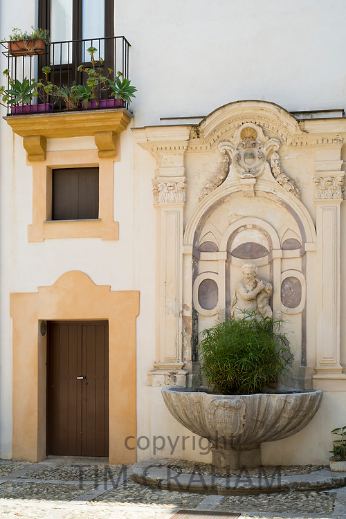 Typical Sicilian palazzo courtyard and ornate architecture with cast iron balcony and cobble stones paving in city of Palermo, Sicily, Italy