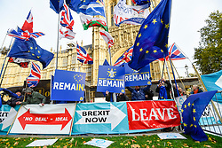 © Licensed to London News Pictures. 30/10/2019. LONDON, UK.  Anti-Brexit protesters with signs next to Pro Brexit banners outside the Houses of Parliament. Photo credit: Stephen Chung/LNP
