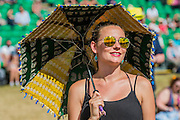 Fans enjoy the sunshine, with protection from a parasol, as Laura Mvula plays the Obelisk Stage - The 2016 Latitude Festival, Henham Park, Suffolk.