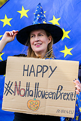 © Licensed to London News Pictures. 30/10/2019. London, UK. A Brexit protester holds a'HAPPY #NO HALLOWEEN BREXIT' sign outside Houses of Parliament. On Tuesday 29 October 2019 MPs voted for a UK general election on 12 December 2019. Photo credit: Dinendra Haria/LNP