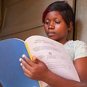 LÉGENDE: Edem en train de ranger ses assiètes après un petit déjeuner matinal. Elle prépare son départ pour le chantier. LIEU: CERFER, Lomé, Togo. PERSONNE(S): Alema Edem Djagbo (à droite).