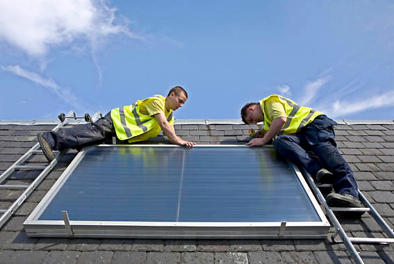 Workmen installing a solar thermal panel on the roof of Pinmore ceramics gallery, they have received advice from the Energy agency, Ayrshire..Solar water heating systems use heat from the sun to work alongside your conventional water heater