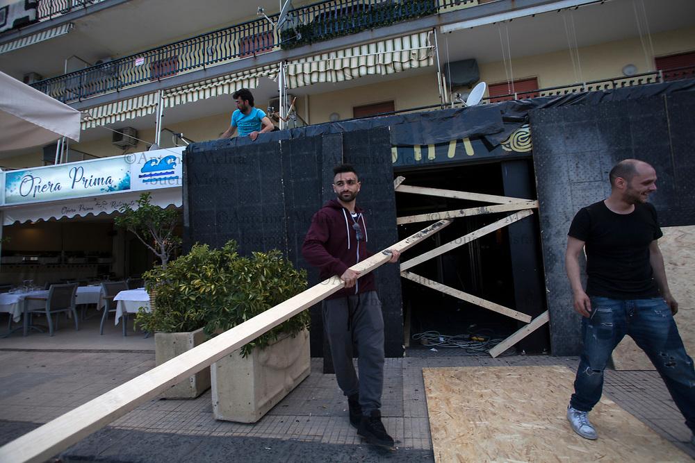 Commercianti, intimoriti dal corteo No G7 di sabato,  proteggono ingressi e vetrine dei propri negozi con assi di legno.