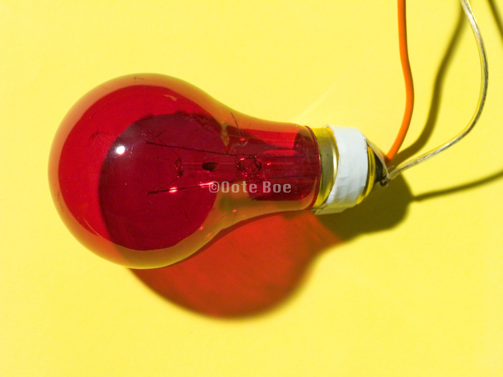 a red light bulb with wires taped to it