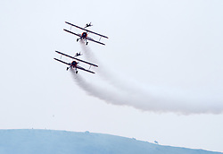 © Licensed to London News Pictures. 23/06/2019. Weston-super-Mare, North Somerset, UK. Aerosuperbatics Wingwalkers display on an overcast day at the Weston Air Festival taking place over the weekend of 22 and 23 June in Weston Bay. Earlier the Red Arrows display was aborted after only a few formations due to low cloud cover. Photo credit: Simon Chapman/LNP.