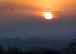 © Licensed to London News Pictures. 13/02/2017. Guildford, UK.  The sun rises over Surrey viewed from Newlands Corner near Guildford.  Sunshine and warmer temperatures are expected in the south today after the recent cold spell.  Photo credit: Peter Macdiarmid/LNP