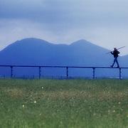 Worker walking on top of satellite array in open, grassy field in San Diego County.