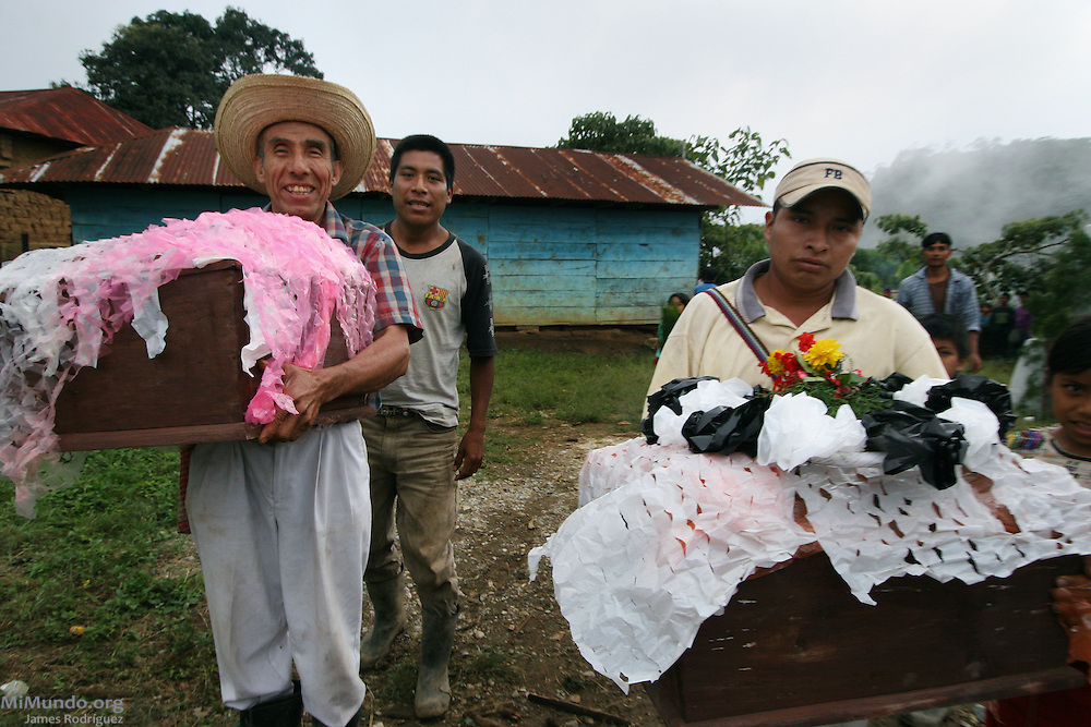 Ixil Mayan community members from Xaxmoxan collect the temporary coffins holding the remains of their family members killed during the Guatemalan internal armed conflict. The National Coordination for Guatemalan Widows (CONAVIGUA) and the Forensic Anthropological Foundation of Guatemala (FAFG) returned the remains of 14 wartime victims to their respective family members in the hamlet of Xaxmoxan, Chajul, up in the Ixil Mayan highlands of Quiché after successful exhumations of clandestine mass graves. Most of the victims perished in the mountainside between 1980 and 1983 as they fled the Army's brutal Scorched Earth campaign against a civil population accused of supporting the guerrilla groups in the region. Xaxmoxan, Chajul, Quiché, Guatemala. January 25, 2007.