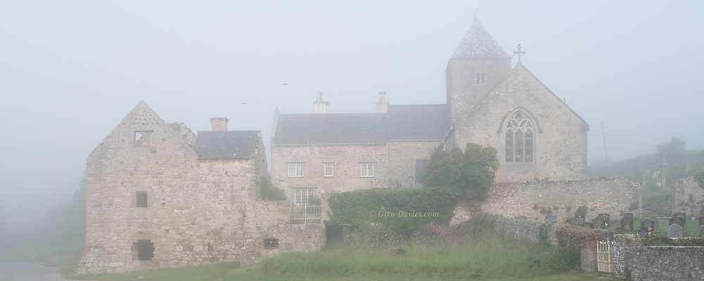 Very early morning fog surrounds the historical church and priory at Penmon. Two early birds catch the thermals as gentle sunshine warms the cool air.