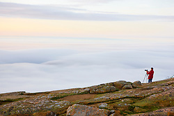 A photographer above the fog on the summit of Cadillac Mountain in Maine's Acadia National Park.